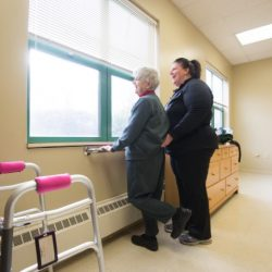 senior day services staff helping elderly woman look out window