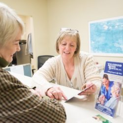 Elderly woman looking over senior activity brochures