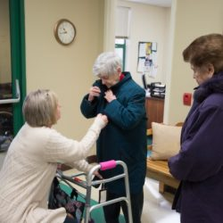 staff at Senior Day Services helping elderly woman put on coat