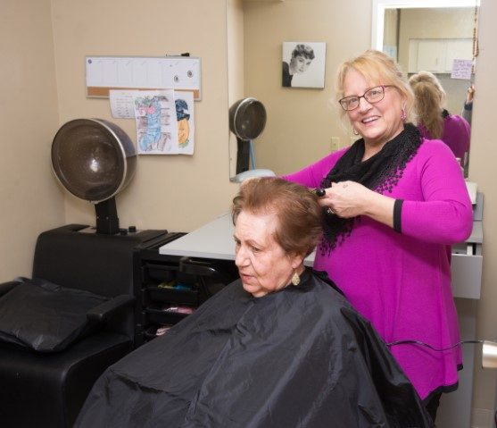 elderly woman receiving haircut at senior day services