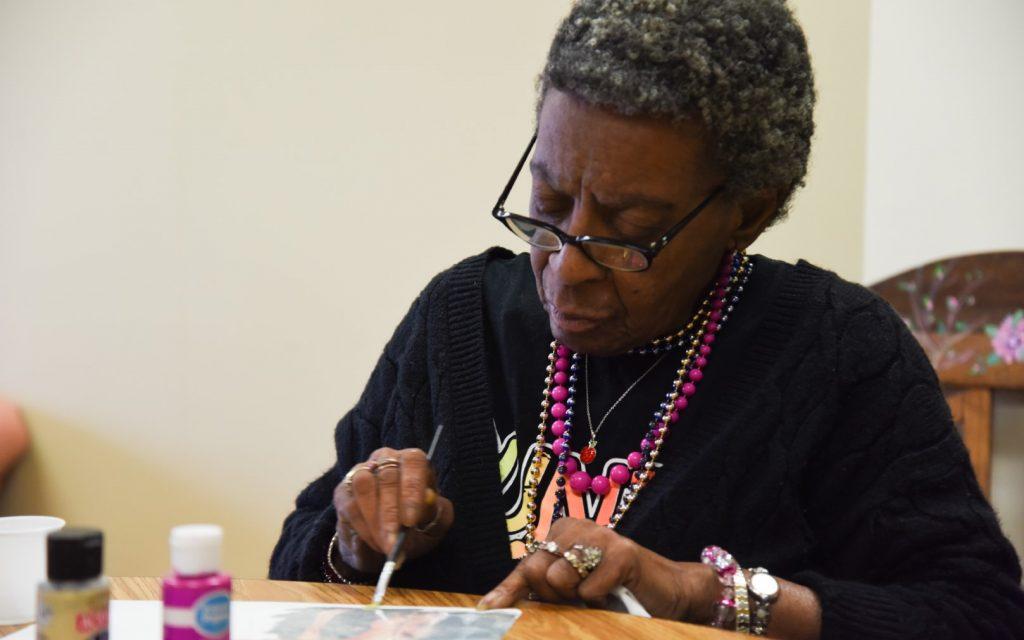elderly woman painting during senior activities