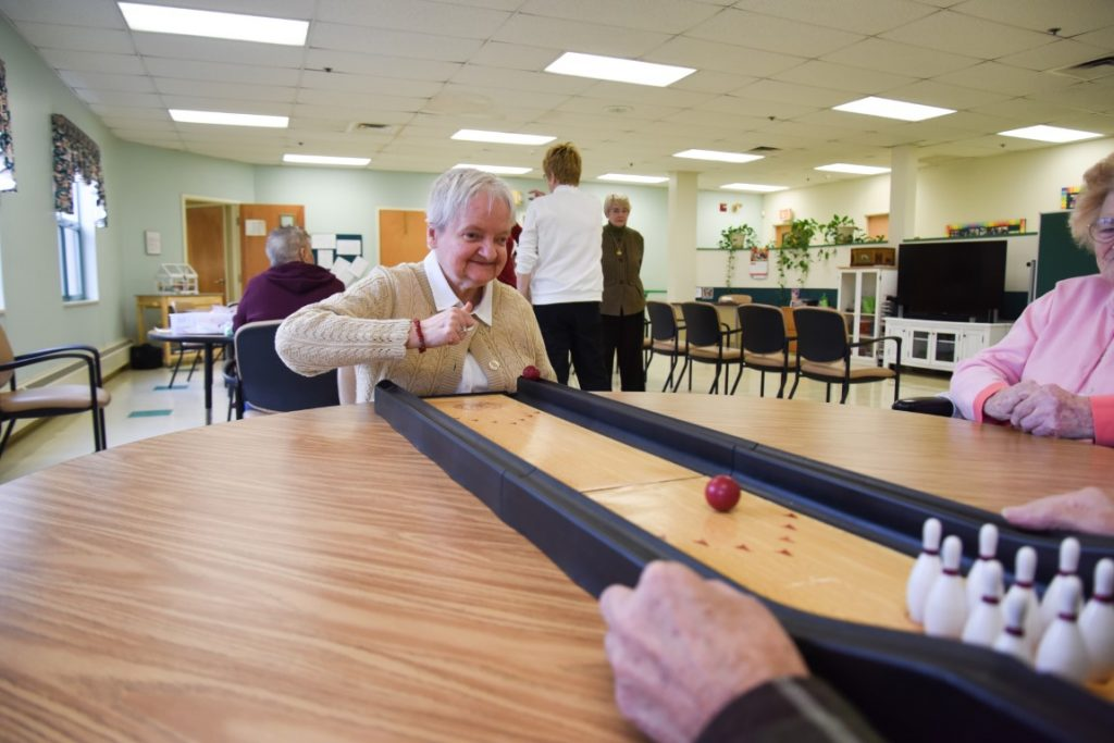 elderly woman playing mini bowling at Senior Day Services
