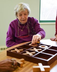 elderly woman playing tic-tac-toe at senior day services
