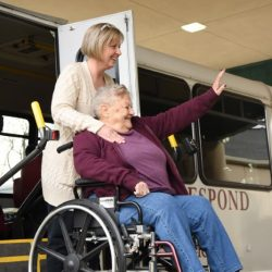 woman in wheelchair waving to staff at Senior Day Services