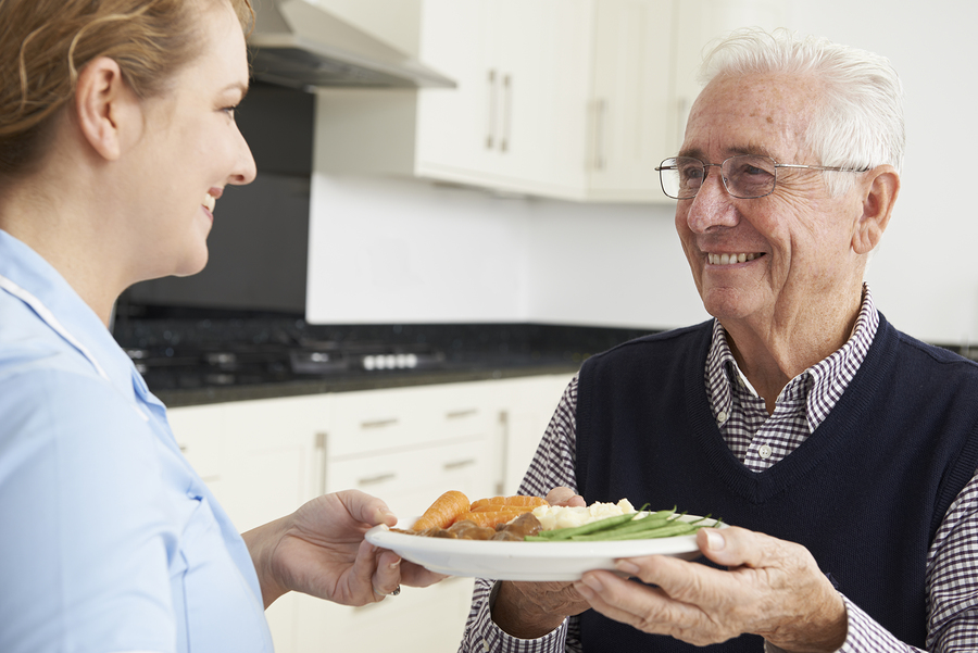 Carer Serving Hot Meal to Senior Man at Senior Day Services