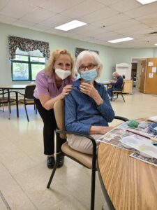 elderly woman and nurse posing beside craft at senior day services